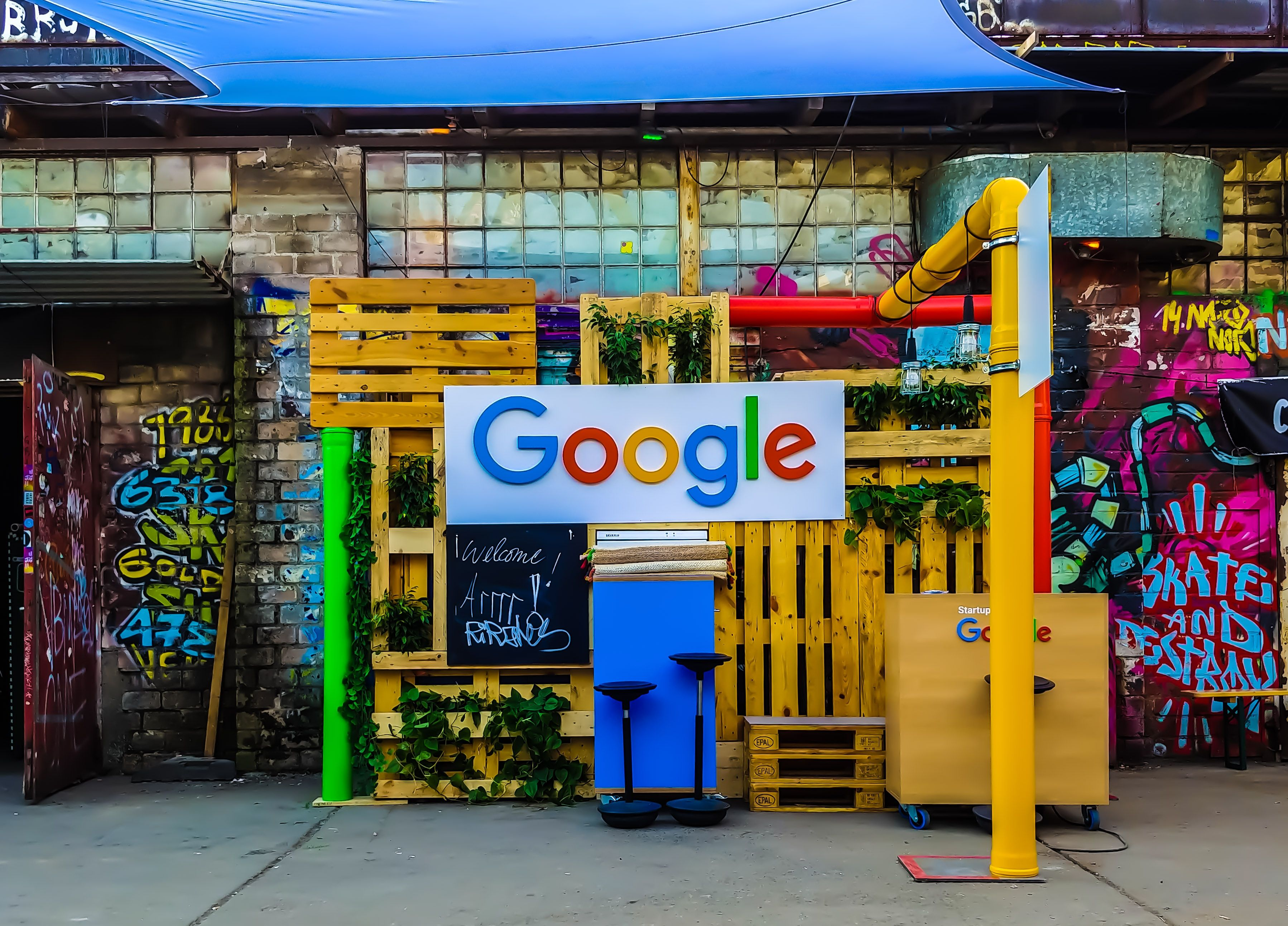 Google logo with busy bright background and graffiti on street